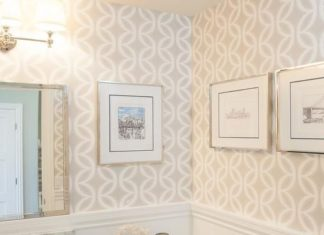 Chic powder room features top half of walls clad in beige geometric wallpaper an...
