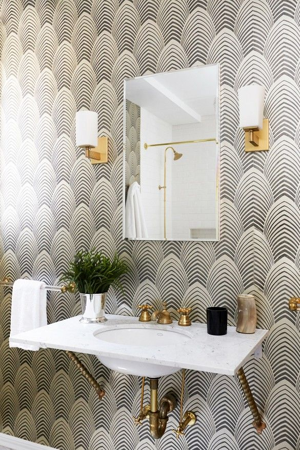 Powder room with black and white Art Deco wallpaper, wall mount sink, brass