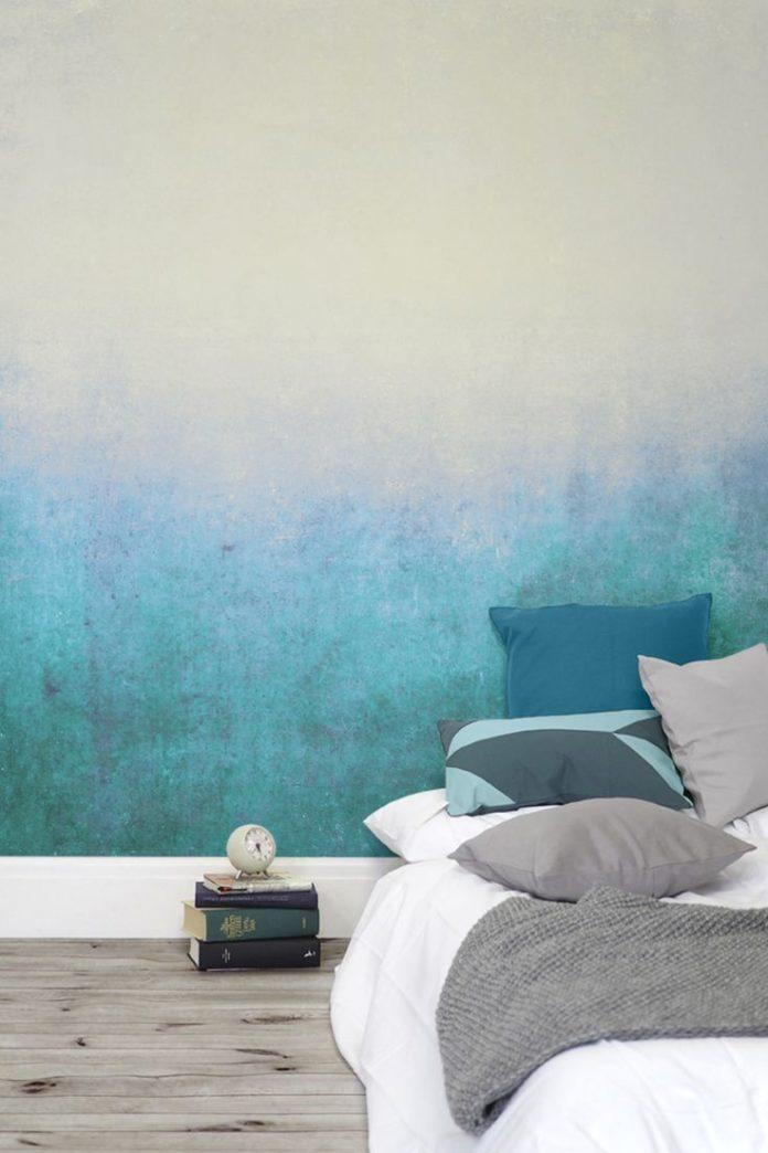 Deep blues gently fade into green tones. This subtle ombre wallpaper design crea...