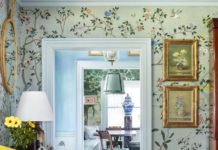 A de Gournay floral festoons the walls of the dining room. Slipper chairs wear a...