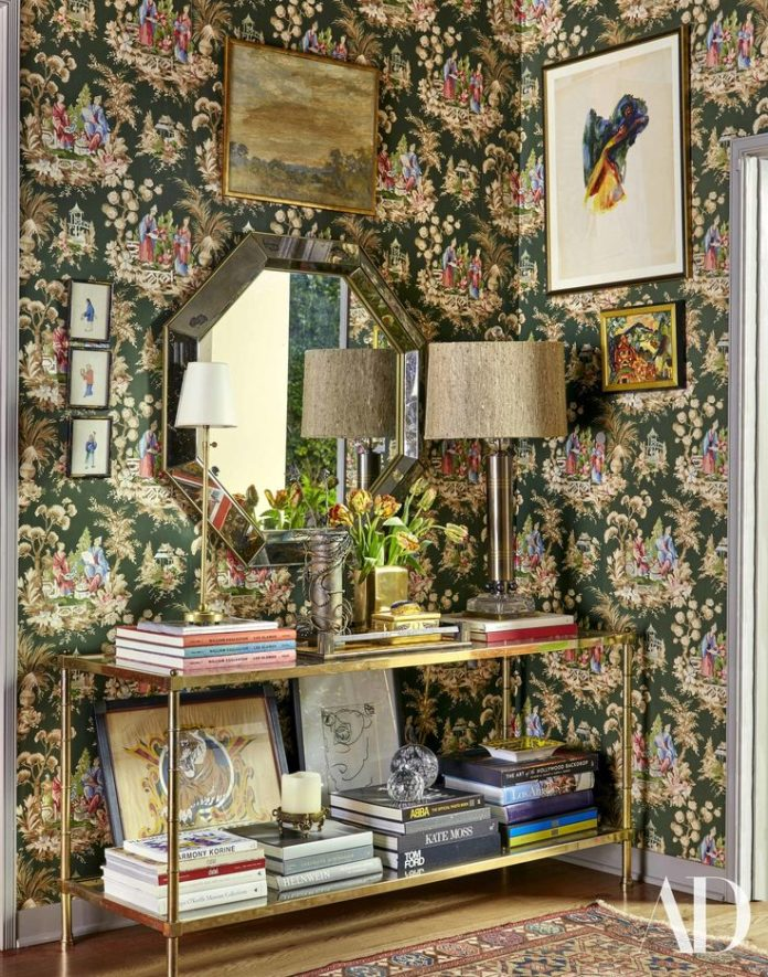 Vintage wallpaper adds a pop of pattern to the foyer. Vintage console lamp and m...