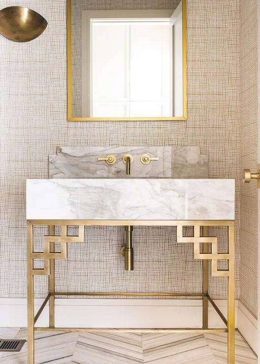 Fixed on a wall covered in tan textured wallpaper a gold sconce lights a gold be...